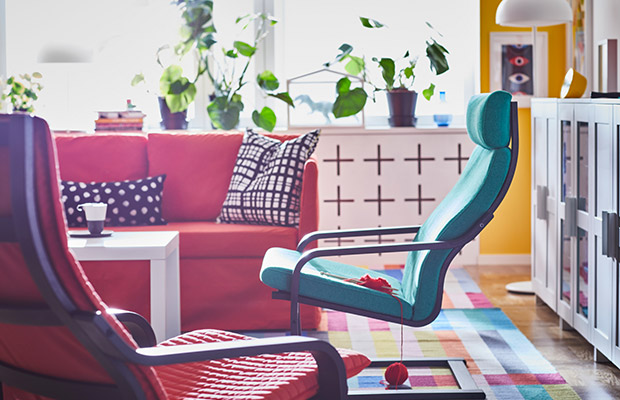 An IKEA classic: Two POANG Armchairs in bright green and orange displayed in a fun, bright, colourful living room.