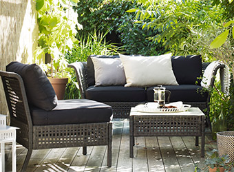 KUNGSHOLMEN couch displayed with black cushions in a bright, backyard patio.