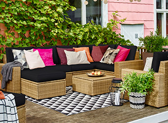 SOLLERON couch with black cushions displayed in a bright, outdoor entertainment area..