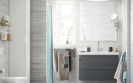 A bathroom sink and grey cabinet, mirror and long white cupboard in a grey-tiled room.
