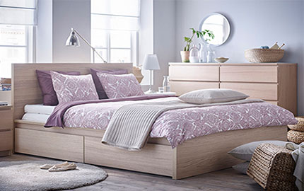 A wooden bed with white and purple bedding and a side table, chest of drawers in a white room.