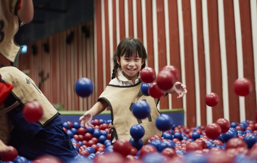 A smiling little girl playing in an indoor play area.