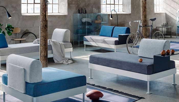 DO YOUR THING with the new and exclusive, modular DELAKTIG sofa and/or couch designed by IKEA in collaboration with Tom Dixon. Pastel grey and blue couches displayed in a large, eerie room with conrete walls.
