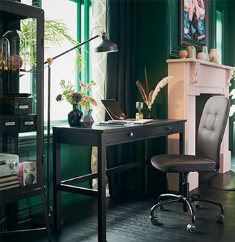 A  black brown desk by the window in a sitting room with green walls and a pink fireplace.