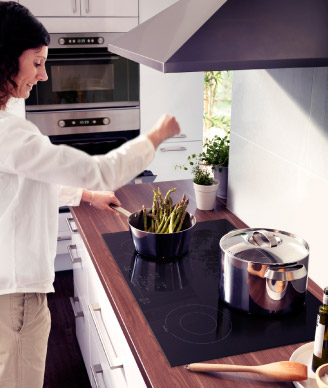 woman cooking on energy efficient induction cooktop from IKEA