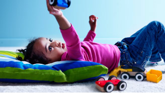 girl lying on floor playing with IKEA toy cars