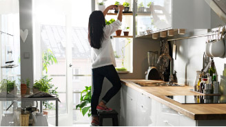 IKEA kitchen with woman standing on stool reaching for herbs