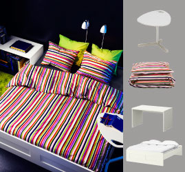 Brightly coloured bed linen with bold stripes, DAVE computer table in white and two TRÅL wall lamps.