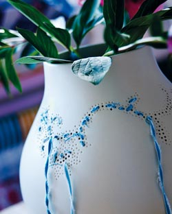 A white vase with blue yarn woven through decorative holes.
