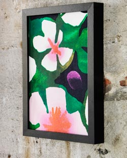 Colourful floral fabric framed and displayed on a wall.