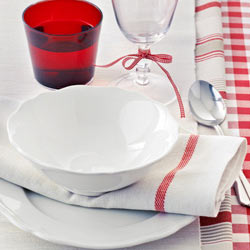 White linen napkin with red stripe set under a white bowl.