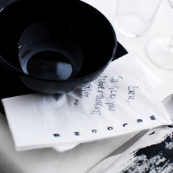 A white paper napkin with a message handwritten in black ink.