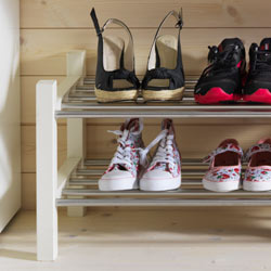 A white and metallic shoe rack with shoes.