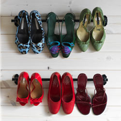 Pairs of high heels hanging from two wall- mounted rails.