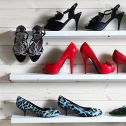 High heels stored on three narrow, wall- mounted shelves.