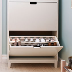 A white shoe cabinet with open drawer, showing stored shoes.