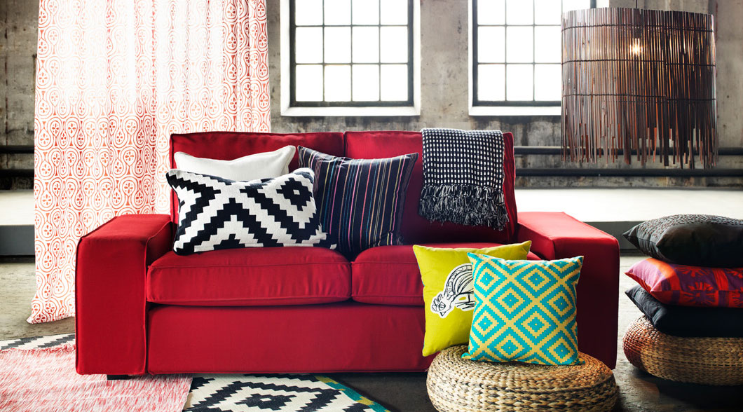 Red KIVIK sofa and cushions with bold colours and patterns.
