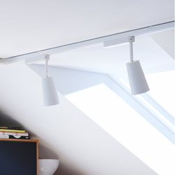Two spotlights with white shades on a ceiling track