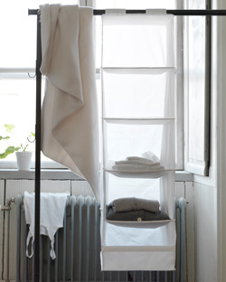 A few folded shirts in SKUBB hanging shelves, suspended from a rod.