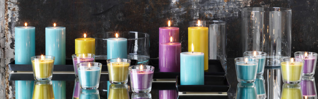 Lit block candles in lilac, blue-grey and yellow-green