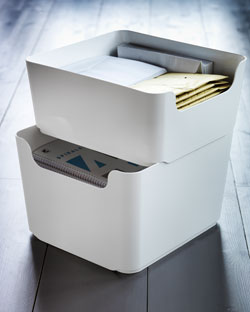 Two white bins, stacked, filled with envelopes and notebooks.