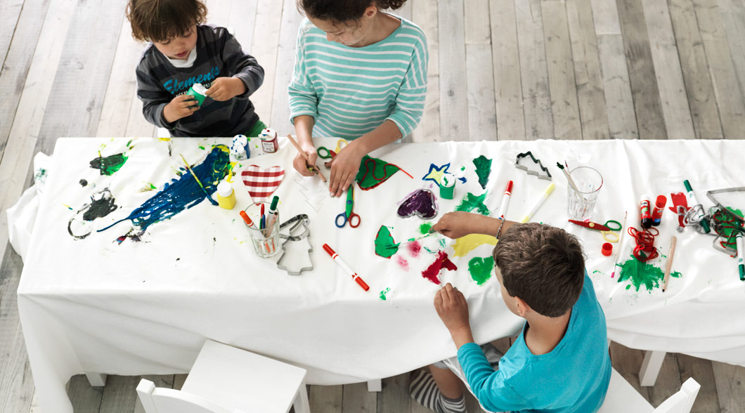 Kids decorating a tablecloth.