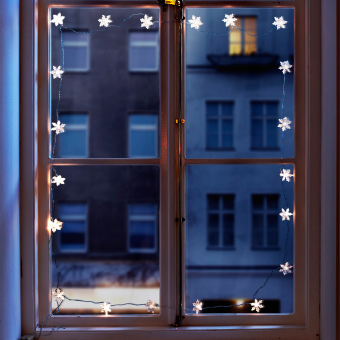 STRÅLA snowflake light chain decorating a window