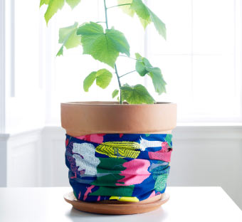 FJÄLLFLY multicolour textile wrapped around RÖNNBÄR plant pot.