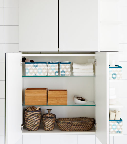 Open bathroom cabinet with boxes and baskets inside