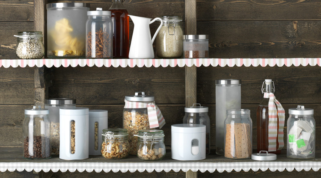 Pantry shelf with jars and tins including DROPPER jars with lids.