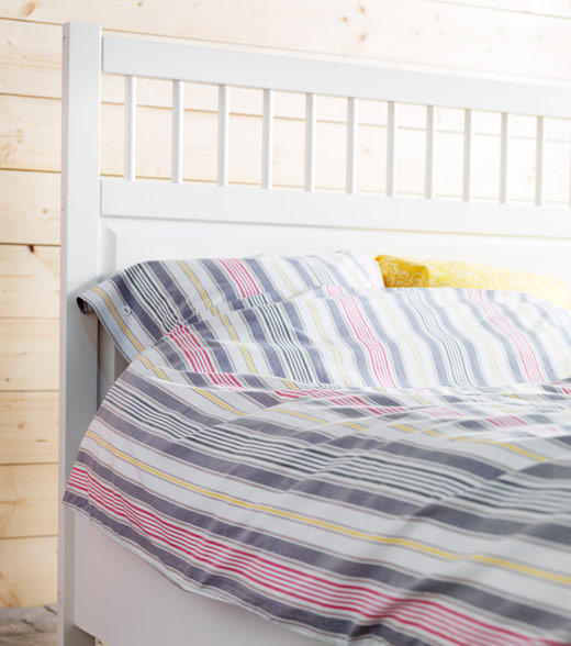 Quilt cover set with stripes in a white wooden bed