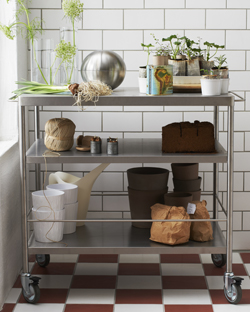 FLYTTA kitchen trolley filled with plant pots, vases and watering can