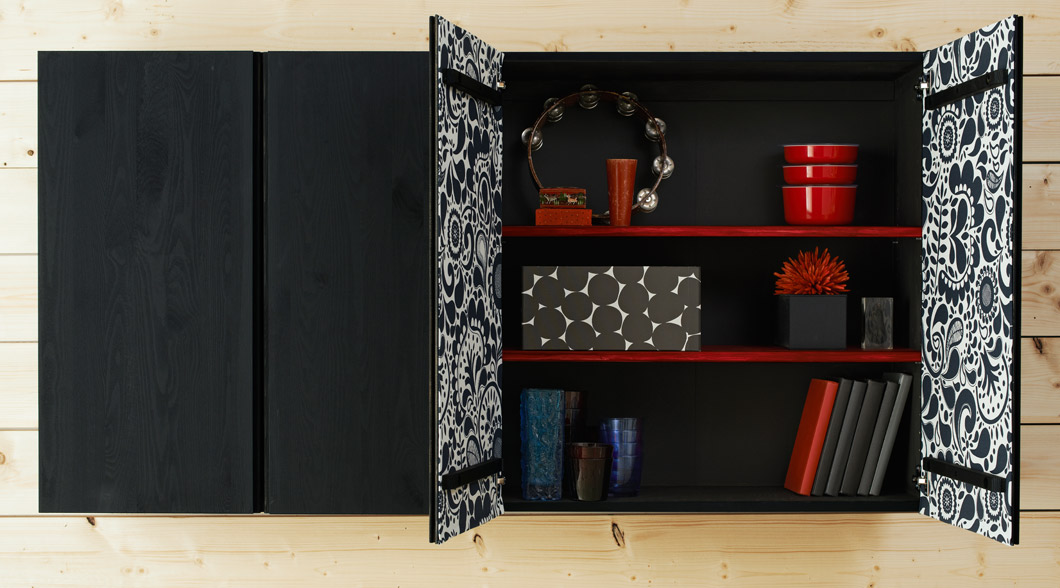 Wooden cabinets painted black with red shelves and with patterned fabric on the inside of the doors