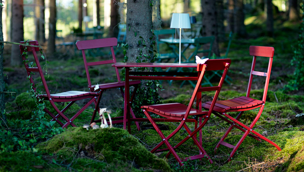 Red MÄLARÖ table and chairs in a woodland setting