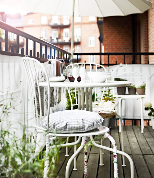 White LÄCKÖ table and chairs on a balcony