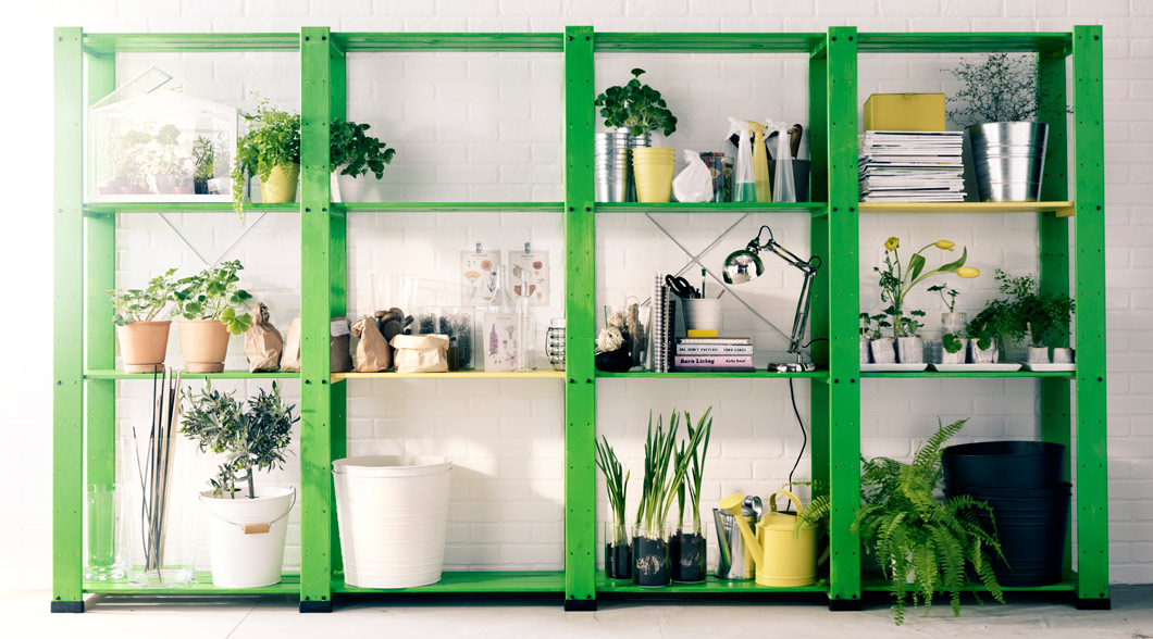 Four wooden shelving units filled with plant pots, plants, flowers, vases and watering cans