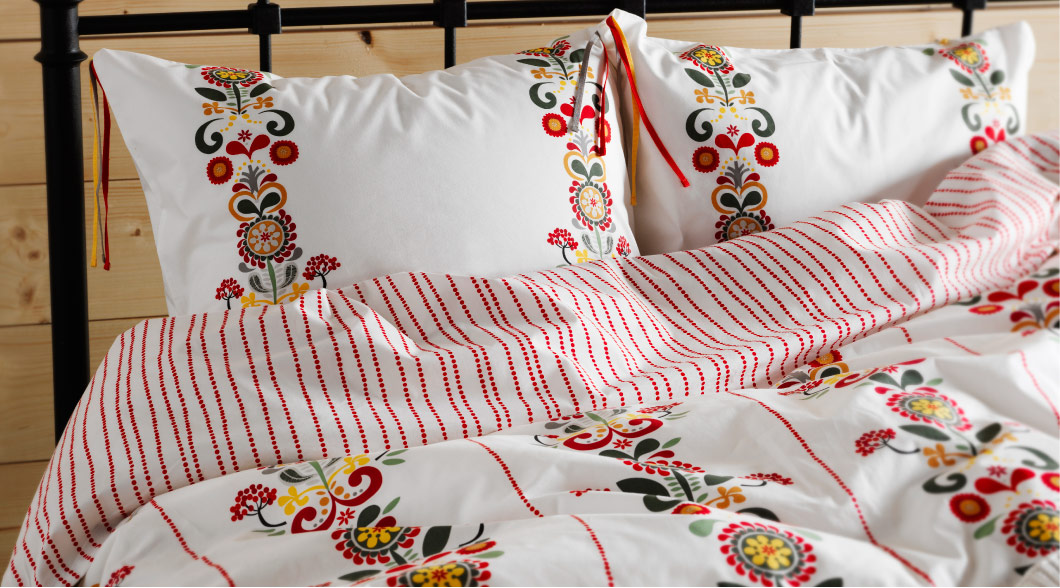 Close-up of ÅKERKULLA quilt cover and pillowcases with flower pattern