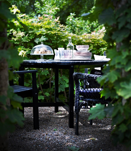 ÄNGSÖ table and chairs sourrounded by a hedge