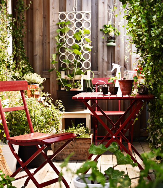 Red MÄLARÖ folding chairs and table in a sunlit patio