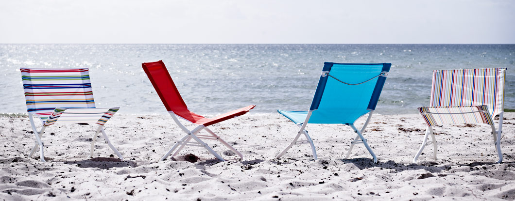 Beach chairs in different colours standing on a sunny beach