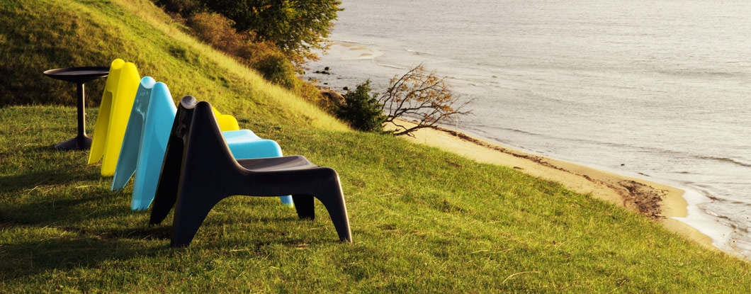 Plastic easy chairs on a hill with the sea in the background