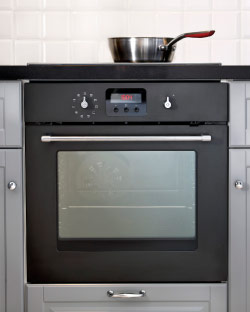 Dark grey forced air oven in a grey kitchen