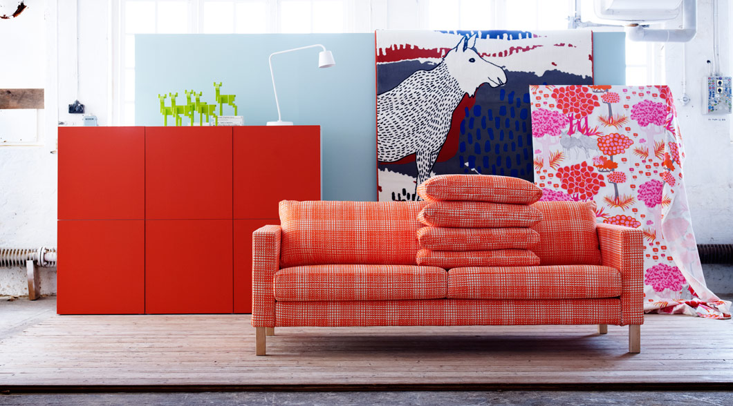 Orange and blue roomset with KARLSTAD sofa, BESTÅ storage, FJÄLLFLY and LUDOVIKA fabrics