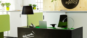 A reception with office furniture in white, green and black