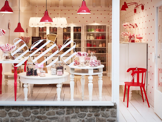 A candy store with white and red tables and storage