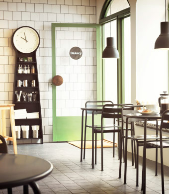 A small café with grey tables and chairs