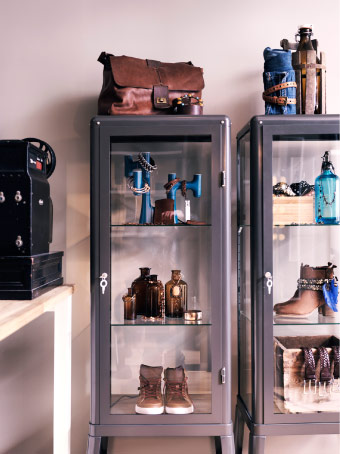 Bottles and shoes displayed in FABRIKÖR grey glass-door cabinet