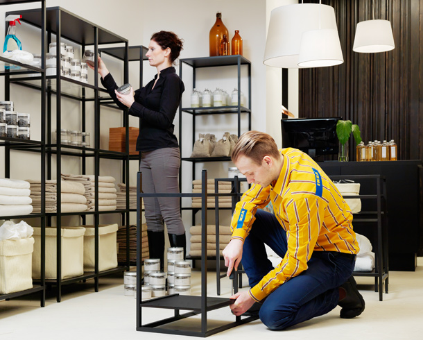 IKEA store staff assembling display and storage furniture