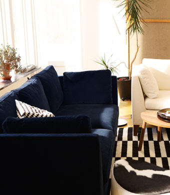 IKEA living room with blue velvet and white cotton three-seat sofas