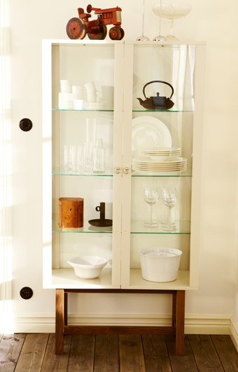 STOCKHOLM glass door cabinet in beige filled with glasses and plates, by IKEA